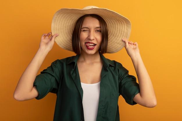 Zelfverzekerde mooie vrouw met strandhoed knippert oog en steekt tong geïsoleerd op oranje muur