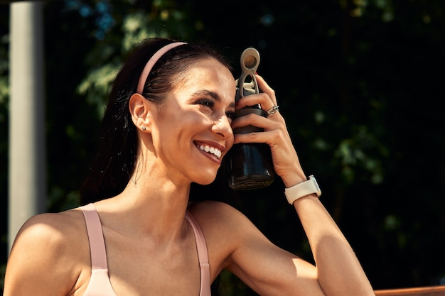 Zelfverzekerde, mooie vrouw rust na training buiten en drinkt water uit een fles, leidt een gezonde levensstijl.