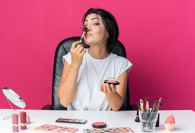 Zelfverzekerde mooie vrouw zit aan tafel met make-uptools die poederblush met borstel op neus aanbrengen