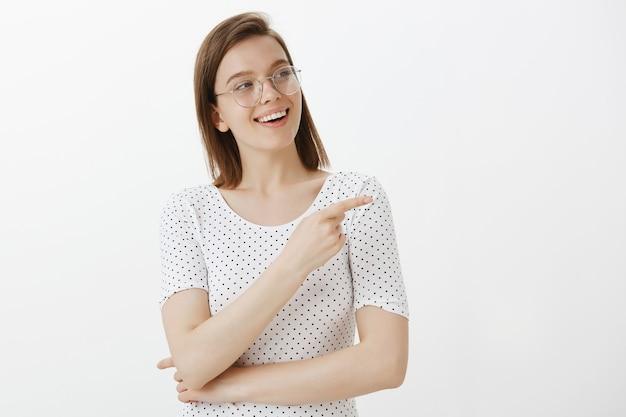 Zelfverzekerde mooie vrouwelijke ontwikkelaar, student die naar rechts wijst, keuze maakt