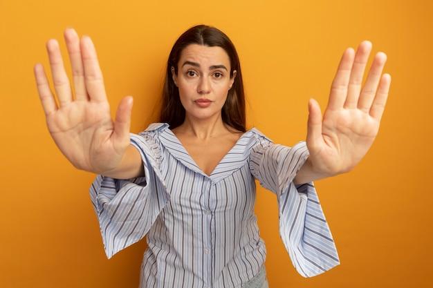 Zelfverzekerde mooie vrouwengebaren stoppen handteken met twee handen geïsoleerd op een oranje muur