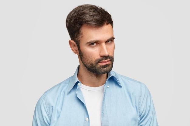 Zelfverzekerde ongeschoren man met donkere haren en haren, luistert aandachtig baas