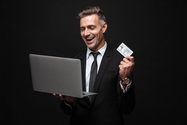 Zelfverzekerde opgewonden aantrekkelijke zakenman die een pak draagt dat geïsoleerd over een zwarte muur staat, een laptop gebruikt en een plastic creditcard toont