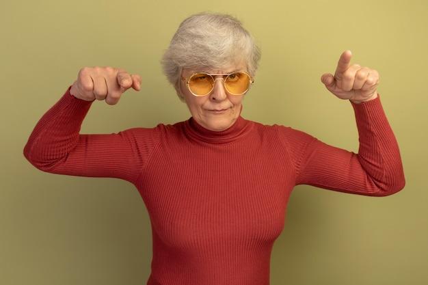 Zelfverzekerde oude vrouw met een rode coltrui en een zonnebril die kijkt en wijst naar de voorkant geïsoleerd op een olijfgroene muur