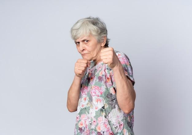 Zelfverzekerde oudere vrouw houdt vuisten klaar om te slaan geïsoleerd op een witte muur