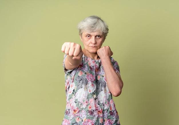 Zelfverzekerde oudere vrouw houdt vuisten klaar om te slaan geïsoleerd op olijfgroene muur