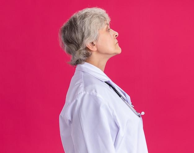 Zelfverzekerde oudere vrouw in doktersuniform met stethoscoop staande zijwaarts geïsoleerd op roze muur met kopieerruimte