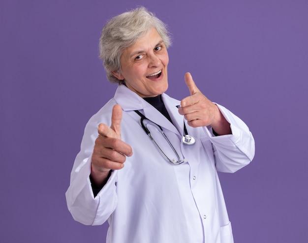 Zelfverzekerde oudere vrouw in doktersuniform met stethoscoop wijzend naar voren met twee handen geïsoleerd op paarse muur