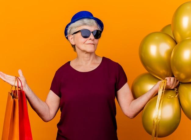 Zelfverzekerde oudere vrouw in zonnebril met feestmuts houdt helium ballonnen en papieren boodschappentassen