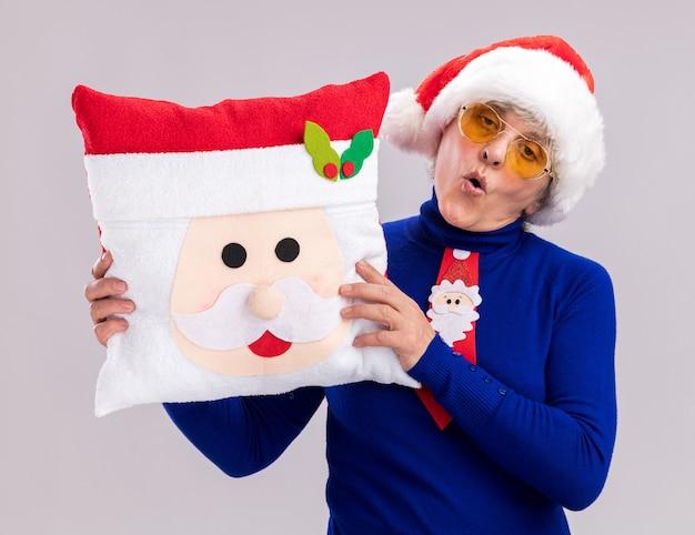 Zelfverzekerde oudere vrouw in zonnebril met kerstmuts en stropdas santa bedrijf santa kussen geïsoleerd op een witte achtergrond met kopie ruimte