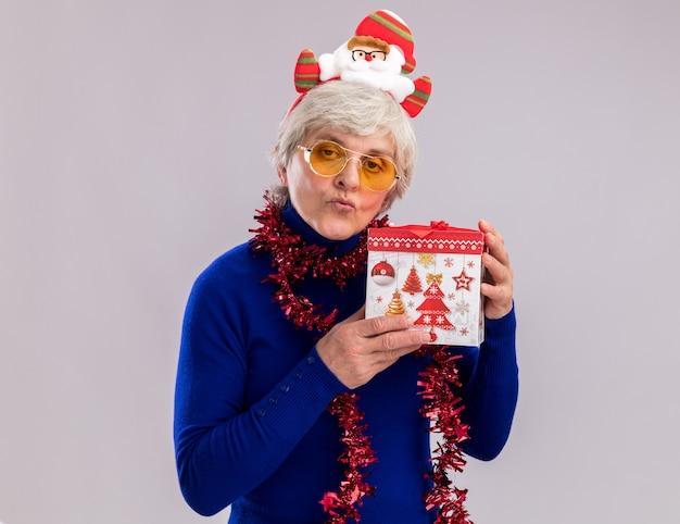 Zelfverzekerde oudere vrouw in zonnebril met santa hoofdband en slinger om de nek houdt de doos van de gift van kerstmis geïsoleerd op een witte muur met kopie ruimte