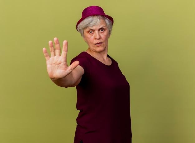 Zelfverzekerde oudere vrouw met feestmuts gebaren stoppen handteken geïsoleerd op olijfgroene muur