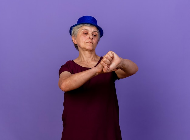 Zelfverzekerde oudere vrouw met feestmuts houdt en kijkt naar arm geïsoleerd op paarse muur