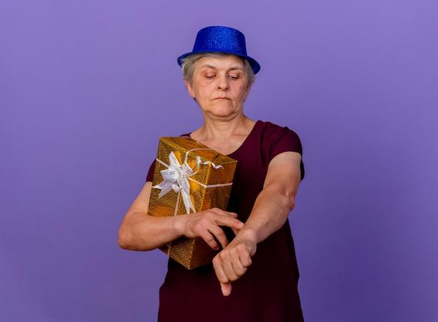 Zelfverzekerde oudere vrouw met feestmuts houdt geschenkdoos kijken arm geïsoleerd op paarse muur met kopie ruimte