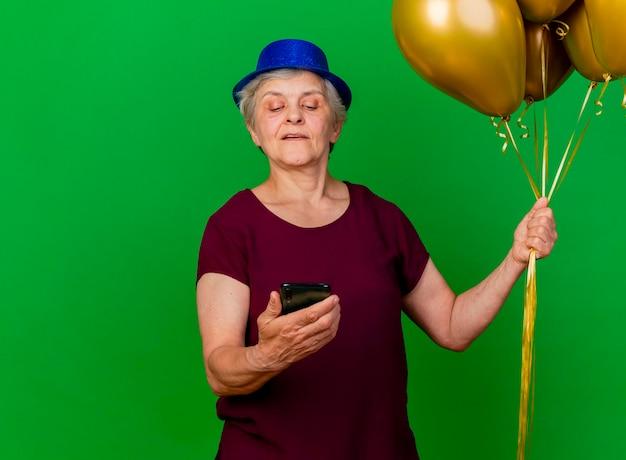 Zelfverzekerde oudere vrouw met feestmuts houdt helium ballonnen en kijkt naar de telefoon op groen