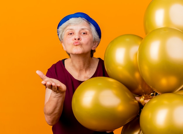 Zelfverzekerde oudere vrouw met feestmuts houdt helium ballonnen vast en stuurt een kus met de hand geïsoleerd op een oranje muur