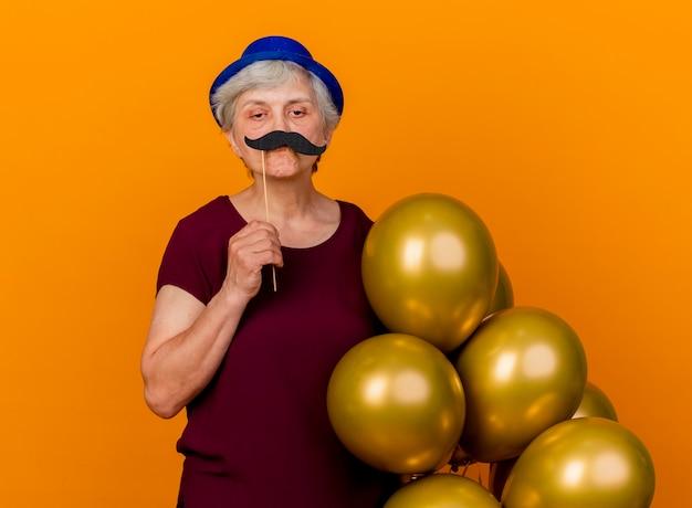 Zelfverzekerde oudere vrouw met feestmuts houdt heliumballonnen en nepsnor op stok geïsoleerd op een oranje muur