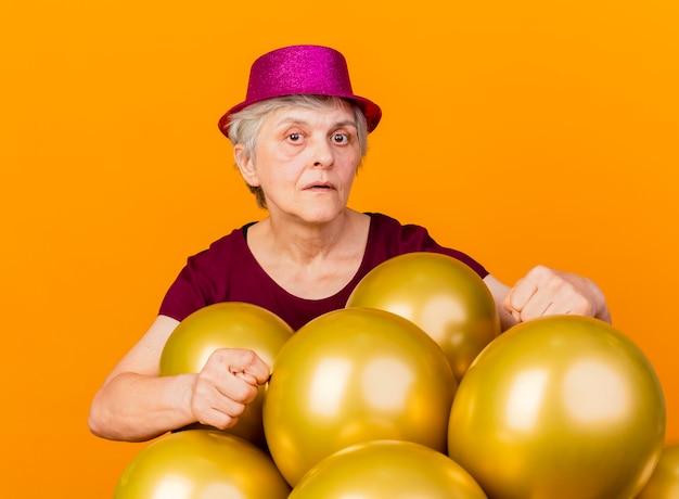 Zelfverzekerde oudere vrouw met feestmuts staat met helium ballonnen gebaren badkamer handteken geïsoleerd op een oranje muur