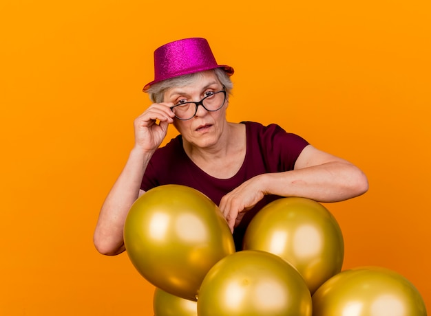 Zelfverzekerde oudere vrouw met feestmuts staat met helium ballonnen vasthouden en kijken naar de voorkant door optische bril geïsoleerd op oranje muur