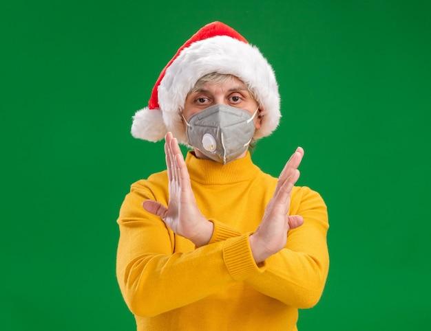 Zelfverzekerde oudere vrouw met kerstmuts dragen medische masker gebaren geen teken met gekruiste handen geïsoleerd op groene achtergrond met kopie ruimte