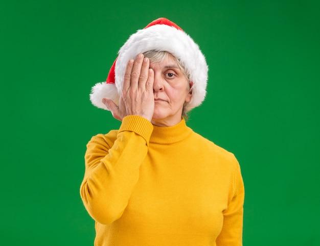 Zelfverzekerde oudere vrouw met kerstmuts voor haar oog met hand geïsoleerd op paarse achtergrond met kopie ruimte
