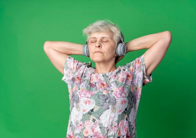 Zelfverzekerde oudere vrouw op koptelefoon staat hand in hand achter het hoofd met gesloten ogen geïsoleerd op groene muur