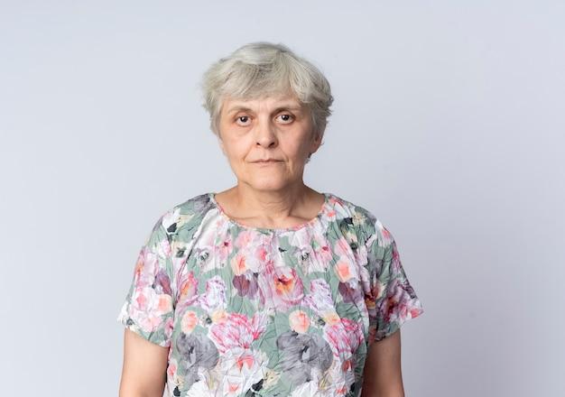 Zelfverzekerde oudere vrouw staat geïsoleerd op een witte muur