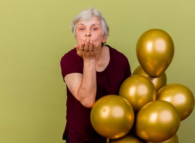 Zelfverzekerde oudere vrouw staat met helium ballonnen verzenden geïsoleerd op olijfgroene muur met kopie ruimte