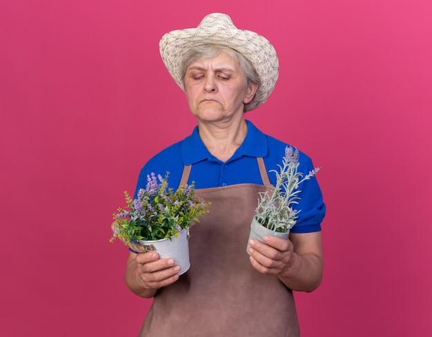 Zelfverzekerde oudere vrouwelijke tuinman die een tuinhoed draagt en naar bloempotten kijkt