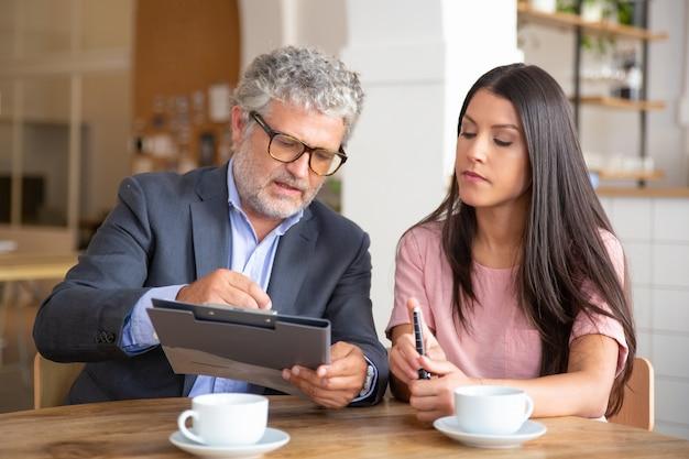 Zelfverzekerde papierexpert die document leest, analyseert en uitlegt aan vrouwelijke klant