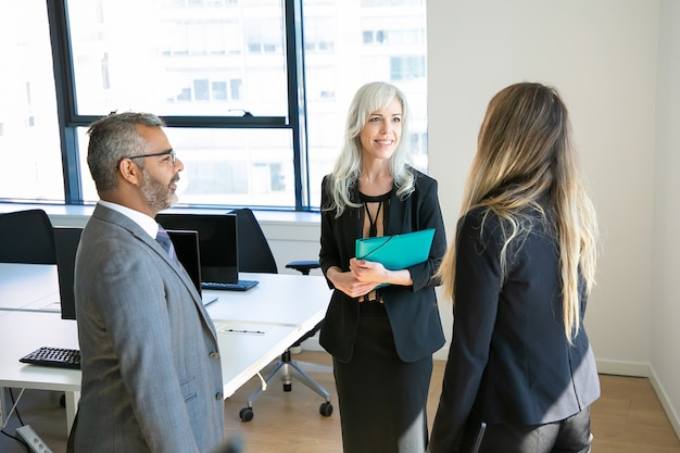 Zelfverzekerde partners bijeen in kantoorruimte, praten en glimlachen. bebaarde baas in brillen project bespreken met mooie zakenvrouwen. bedrijfs-, communicatie- en topmanagementconcept