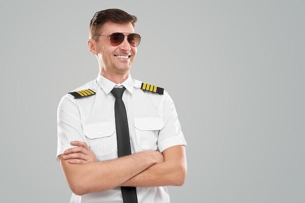 Zelfverzekerde piloot in bevel glimlachend weg