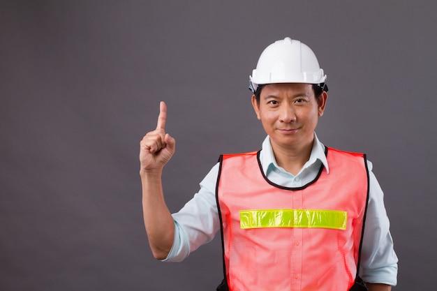 Zelfverzekerde, professionele aziatische man wijzende vinger, concept van mannelijke ingenieur, civiele bouwvakker, bouwer, architect, monteur, elektricien wijzende vinger op lege ruimte