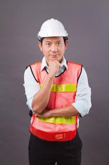 Zelfverzekerde, professionele aziatische mannelijke ingenieursmens denken, een idee plannen. concept van civiele constructie, bouwer, architect, arbeidersdenken