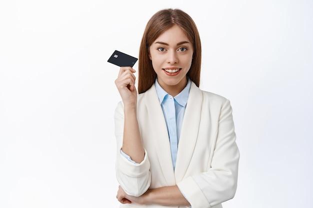 Zelfverzekerde professionele ceo kantoorvrouw toont plastic creditcard, glimlacht en ziet er vastberaden uit, draagt een pak, witte muur
