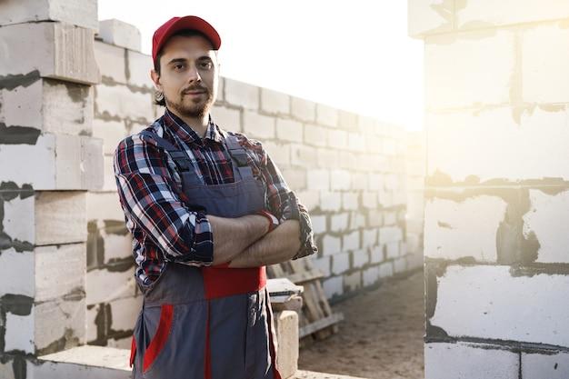 Zelfverzekerde professionele metselaar op de bouwplaats