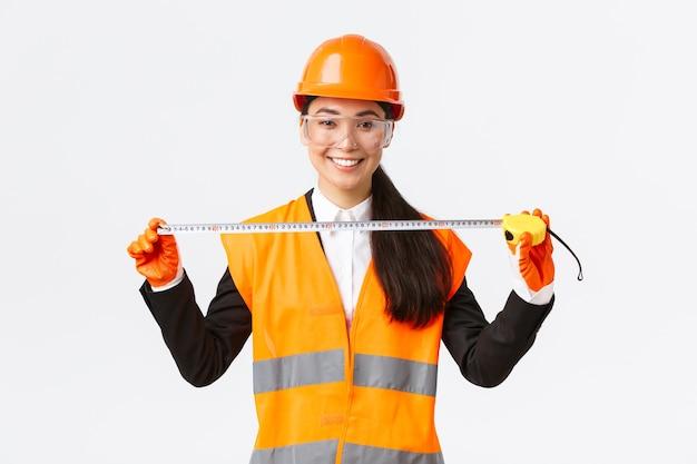 Zelfverzekerde professionele vrouwelijke aziatische architect die lay-out meet, veiligheidshelm en uniform draagt en meetlint vasthoudt, tevreden glimlachend, tevreden met het behaalde resultaat tijdens de bouw
