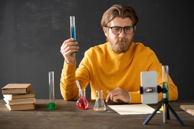 Zelfverzekerde scheikundeleraar in vrijetijdskleding die kolf met blauwe vloeistof aan zijn online publiek toont terwijl hij de kenmerken ervan tijdens de les uitlegt