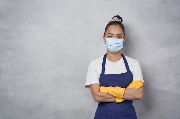 Zelfverzekerde schoonmaakster met rubberen handschoenen en medisch beschermend gezichtsmasker met gekruiste armen, kijkend naar de camera terwijl ze tegen een grijze muur staat. schoonmaakdiensten tijdens covid 19 pandemie