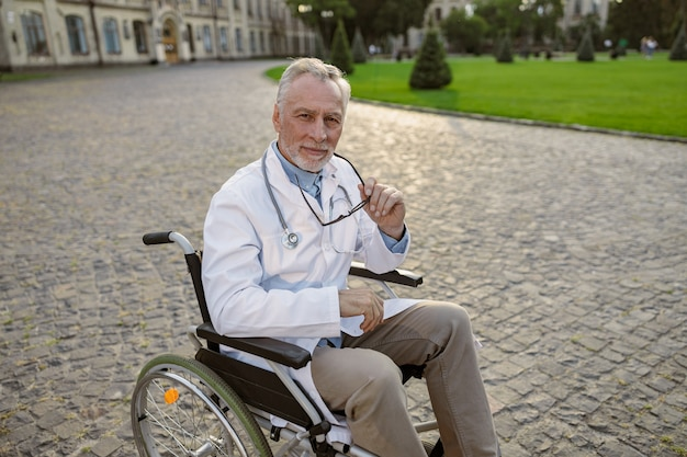 Zelfverzekerde senior gehandicapte mannelijke arts in rolstoel met laboratoriumjas en bril kijkend naar
