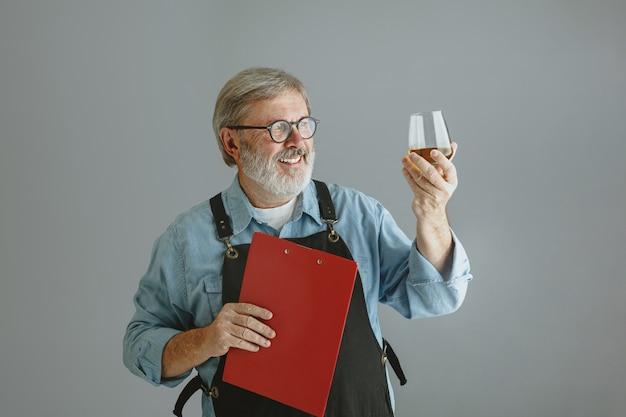 Zelfverzekerde senior man brouwer met zelfgemaakt bier in glas op houten vat op grijs