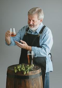 Zelfverzekerde senior man brouwer met zelfgemaakt bier in glas op houten vat op grijze muur. de eigenaar van de fabriek presenteerde zijn producten en testte de kwaliteit.