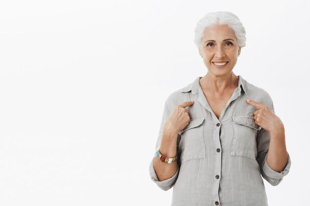 Zelfverzekerde senior vrouw met grijs haar wijzend op zichzelf en lachend