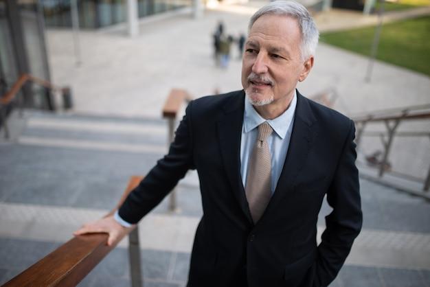 Zelfverzekerde senior zakenman lopen op een trap