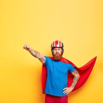 Zelfverzekerde serieuze superheld man heeft bovenmenselijke kracht, maakt vliegend gebaar, klaar om te vluchten en mensen te helpen