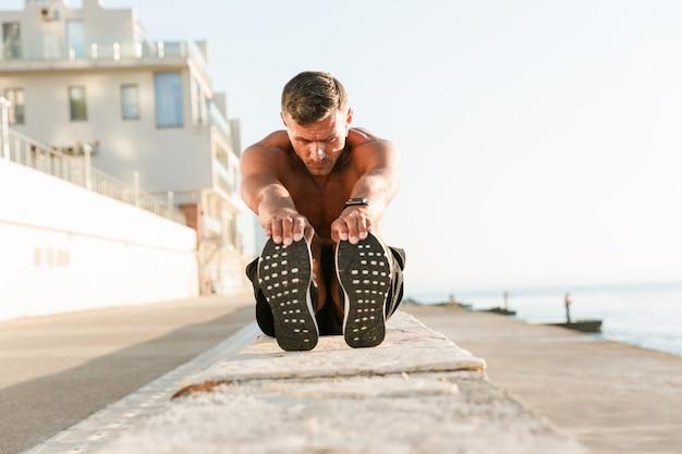 Zelfverzekerde shirtless sportman die rekoefeningen doet