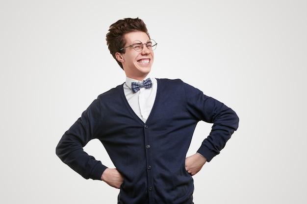 Zelfverzekerde slimme jonge mannelijke student in elegante outfit met vlinderdas en nerdy bril handen op de taille te houden en helder te lachen