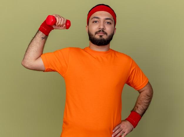 Zelfverzekerde sportieve jongeman met hoofdband en polsband halter verhogen en hand op heup zetten geïsoleerd op olijfgroene achtergrond