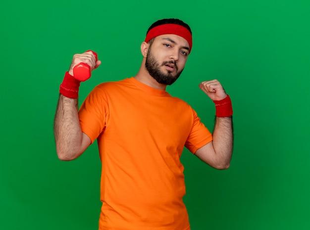 Zelfverzekerde sportieve jongeman met hoofdband en polsband trainen met halter tonen sterk gebaar geïsoleerd op groene achtergrond