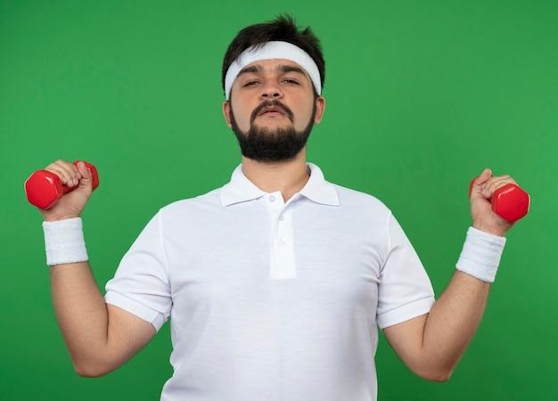 Zelfverzekerde sportieve jongeman met hoofdband en polsband trainen met halters geïsoleerd op groen